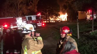 property-owner-debbie-sullivan-confers-with-fire-officials-while-a-120-year-old-home-on-her-property-burns-600x450